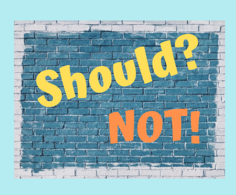 A turquoise brick wall with the word Should and the word Not.