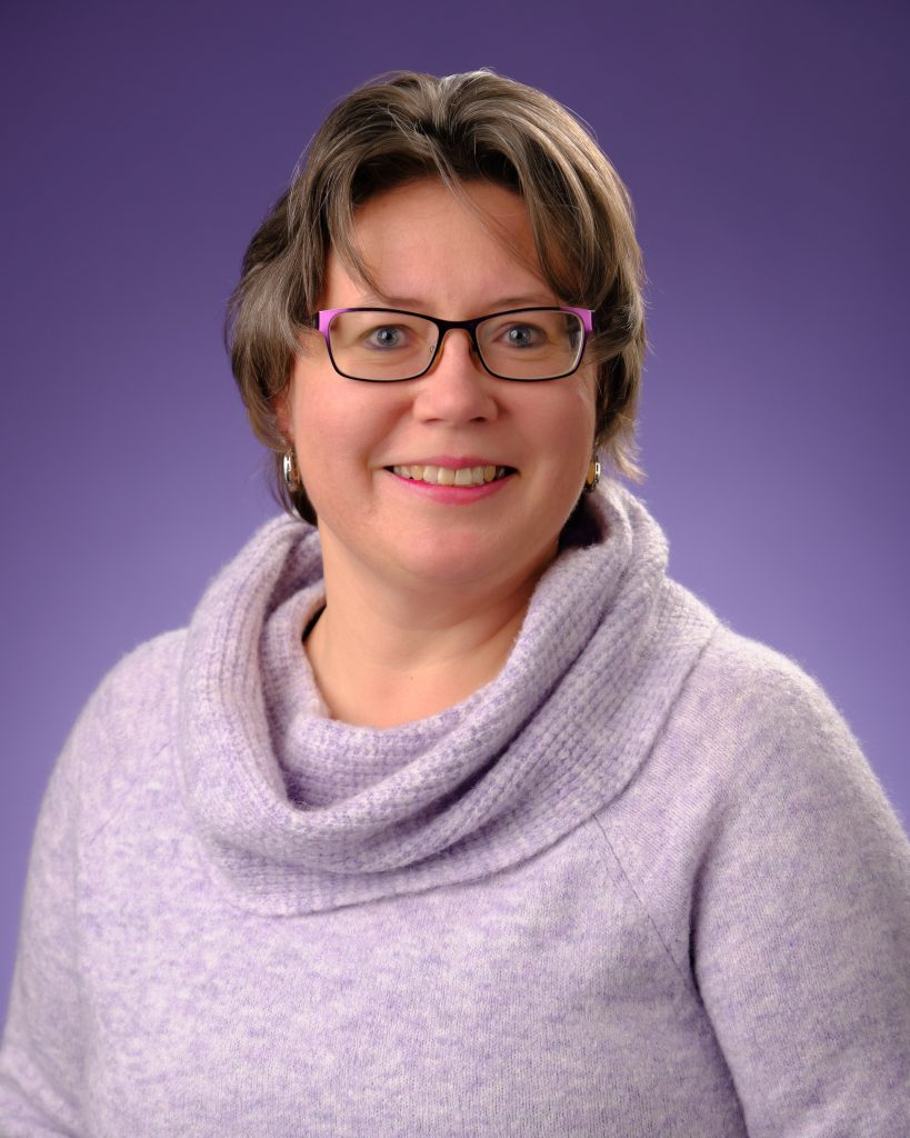 Photo of Tammi Moses wearing a purple sweater with a purple background.